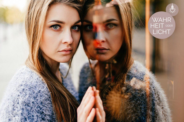 Eine junge, langhaarige Frau mit Dysmorphophobie lehnt sich mit Gesicht und Hand an ein Fenster, in dem ihr Spiegelbild zu sehen ist