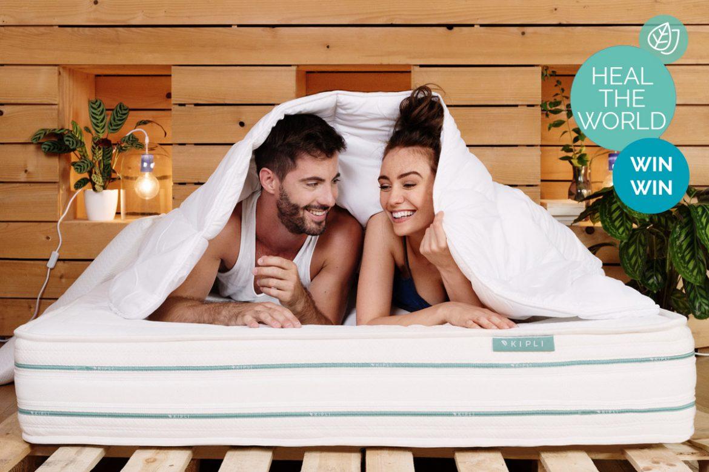 Ein Paar (Mann und Frau) liegt auf einer Naturlatex-Matratze von KIPLI und zieht sich fröhlich die Bettdecke über den Kopf
