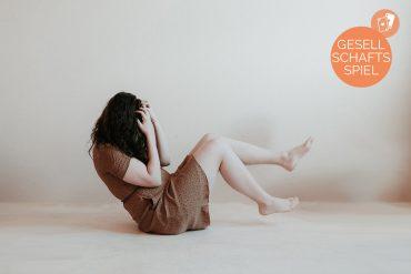 Eine Frau in einem braunen Sommerkleid liegt am Boden und verbirgt ihr Gesicht hinter ihren Händen. Sie wurde Opfer von verbalem Missbrauch.